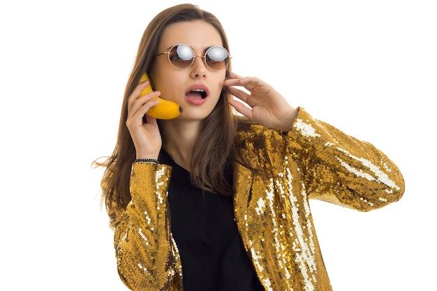 Une femme drôle dans des lunettes de soleil rondes porte une veste dorée et parle en banane comme un téléphone portable isolé sur fond blanc