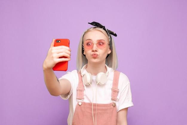 Femme drôle dans des vêtements mignons prend selfie avec grimace sur fond bleu