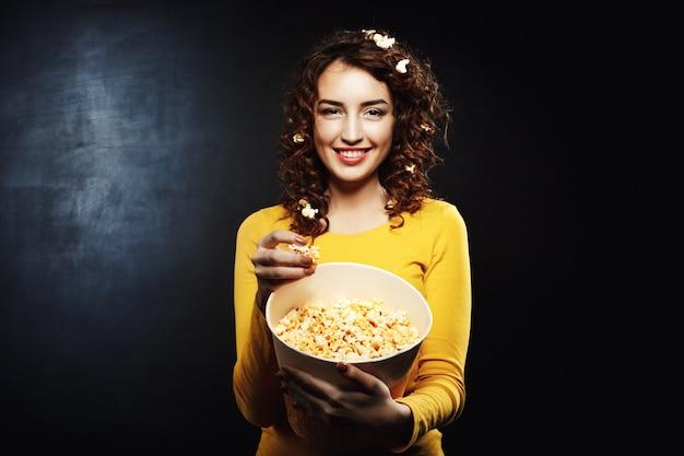 Femme drôle avec du pop-corn sur les cheveux souriant et regardant droit
