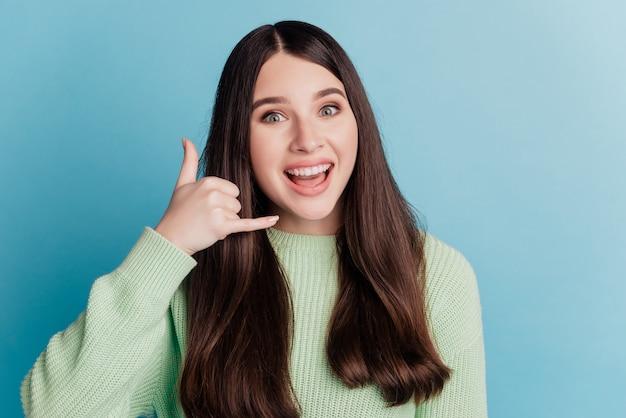 Une femme drôle étonnée et étonnée fait des doigts un signe de téléphone demande un appel sur un mur de sarcelle
