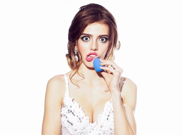 Femme drôle avec des lèvres rouges sur le visage surpris émotionnel grimace tenant une éponge de maquillage isolé sur blanc