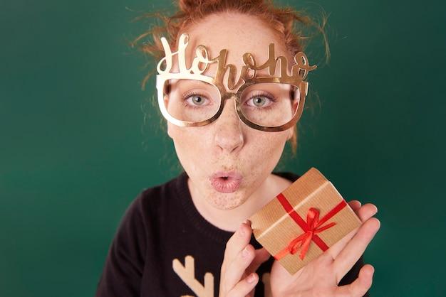 Femme drôle montrant un cadeau de noël