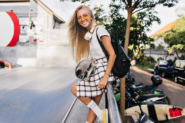 Femme drôle à la peau bronzée posant avec planche à roulettes et riant. portrait en plein air d'une femme blonde sensuelle dans des lunettes de soleil jaunes, profitant de l'été en week-end.