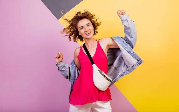 Femme drôle avec des poils courts ondulés dansant et s'amusant sur multicolore.