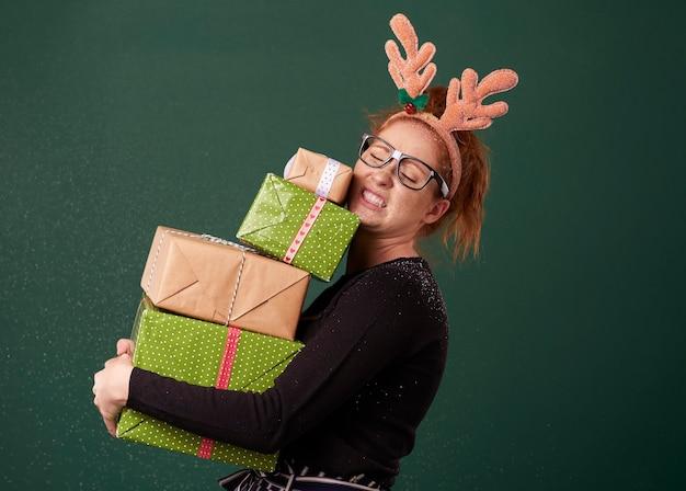 Femme drôle portant pile de cadeaux de noël lourds