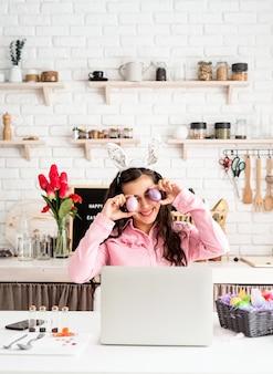 Femme drôle saluant ses amis en ligne, célébrant pâques, couvrant ses yeux avec des œufs colorés