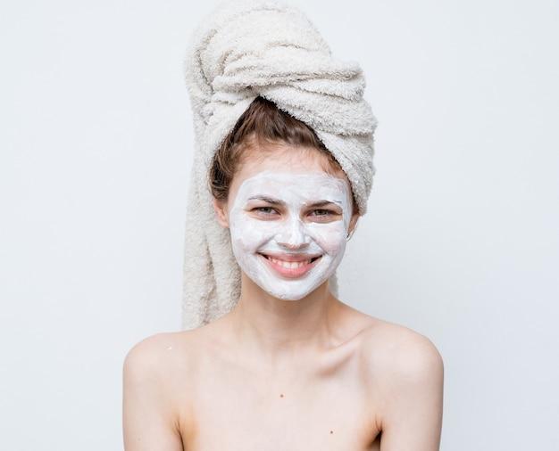 Femme drôle avec une serviette sur la tête épaules nues masque blanc sur le visage.