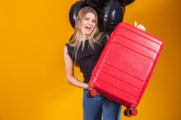 Femme drôle tenant un sac de voyage lourd. anniversaire de promotion de voyage. black friday sur les billets de voyage.