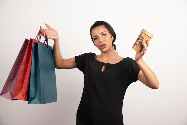 Femme avec du café et des sacs à provisions se sentant perdue sur un mur blanc.