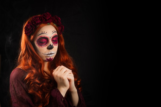 Femme avec du maquillage de crâne de sucre et des cheveux rouges isolés. le jour des morts. halloween.