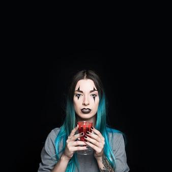 Femme avec du maquillage effrayant tenant gobelet sanglant