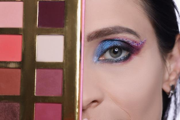 Une femme avec du maquillage de soirée détient une sélection de palette de fards à paupières de concept de cosmétiques