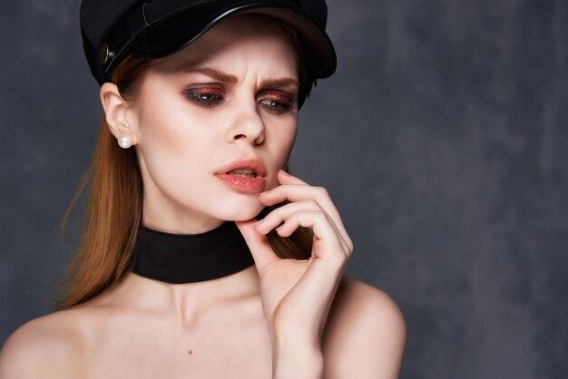 Femme avec du maquillage sur son visage dans un chapeau noir look attrayant fond sombre de luxe