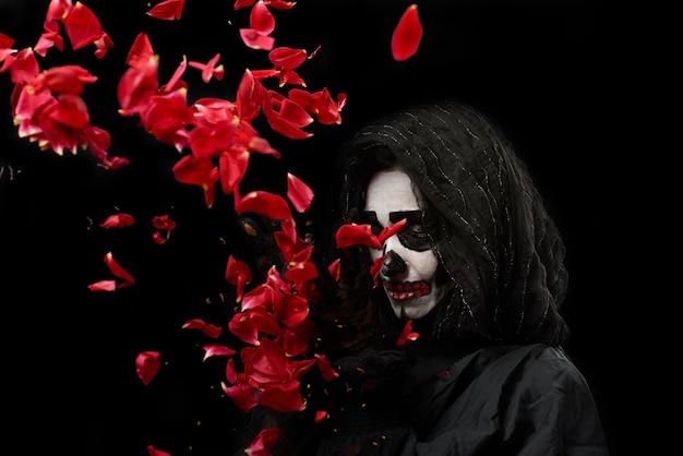 Femme avec du maquillage squelette dans un manteau noir