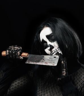 Femme avec du maquillage squelette dans une robe
