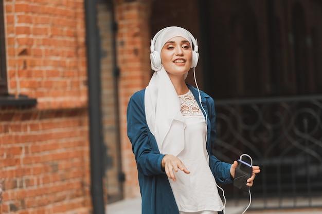 Femme du moyen-orient en hijab écoutant de la musique avec des écouteurs et dansant en plein air femme