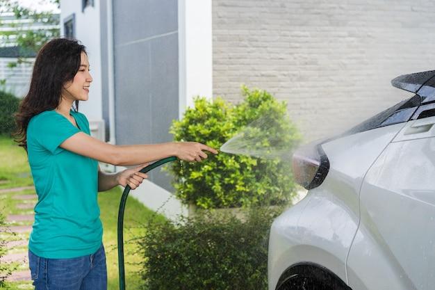 Femme, eau, pulvérisation, voiture, tube eau, lavage