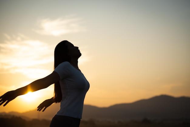 Femme écartant les bras et regardant la montagne, émotions de liberté.