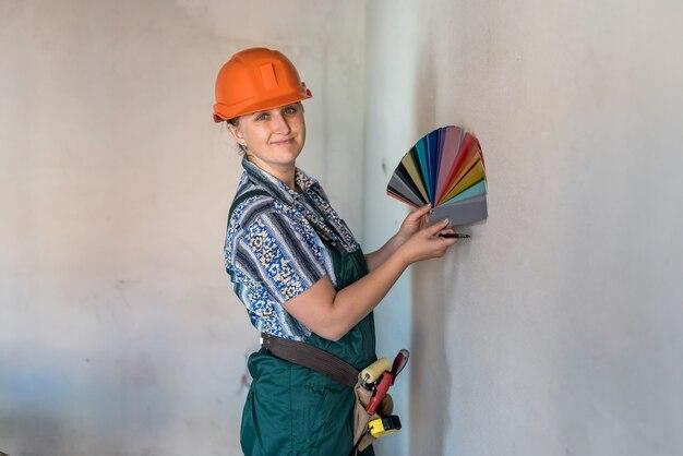 Femme avec échantillon de couleur choisissant la couleur pour peindre les murs