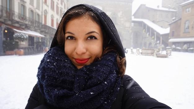 Femme en écharpe chaude et bonnet prendre autoportrait dans la neige d'hiver