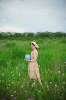 La femme en écharpe avec des pommes contre le pré vert