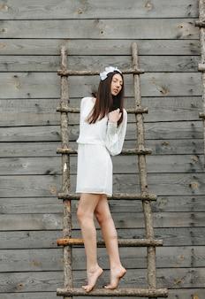 Femme sur une échelle avec les yeux fermés