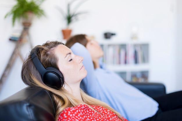Femme écoutant des écouteurs dans le salon