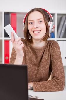 Femme écoutant de la musique au bureau. utilisez l'application sur votre smartphone