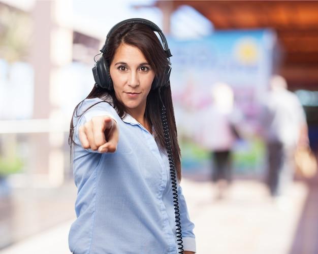 Femme écoutant de la musique avec un casque et pointant vers l'avant