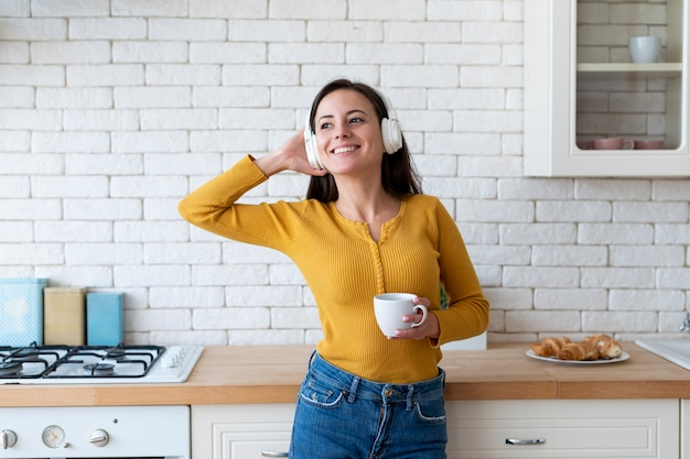 Femme écoutant de la musique en cuisine