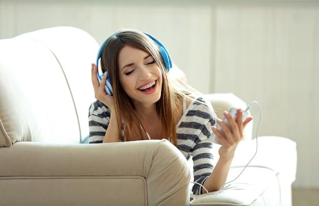 Femme écoutant de la musique dans des écouteurs dans la chambre