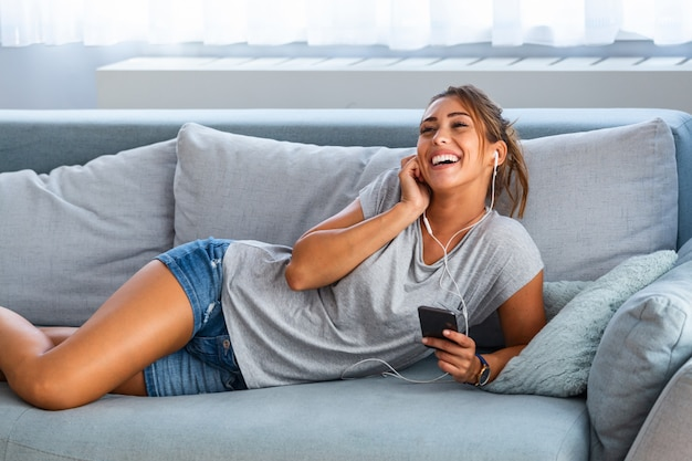 Femme écoutant de la musique dans les écouteurs en position couchée sur le canapé dans la chambre. femme heureuse, ou, adolescente, dans, écouteurs, écouter musique, depuis, smartphone