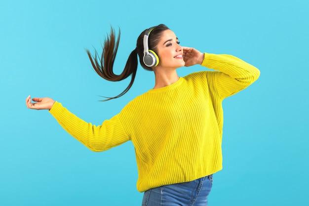 Femme écoutant de la musique dans des écouteurs sans fil heureux portant chandail tricoté jaune posant sur bleu