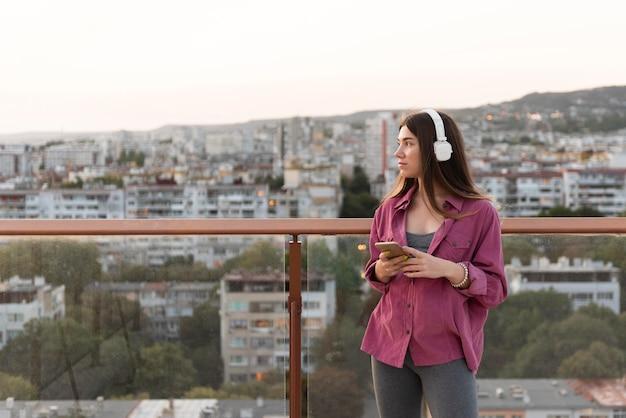 Femme écoutant de la musique dans la ville