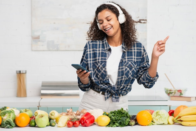 Femme écoutant de la musique et dansant dans la cuisine