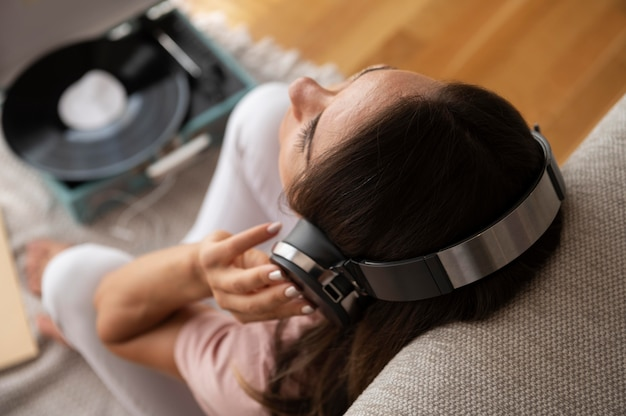 Femme écoutant de la musique avec des écouteurs à la maison