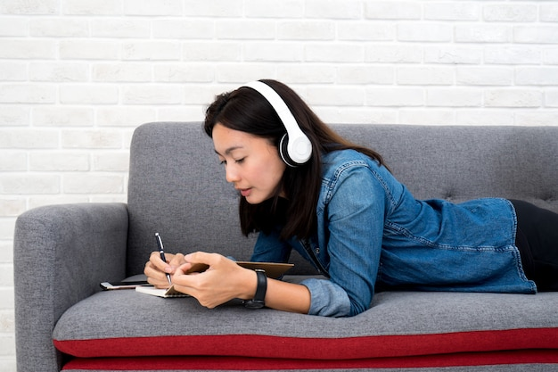 Femme écoutant de la musique et écrivant un journal intime sur un canapé à la maison