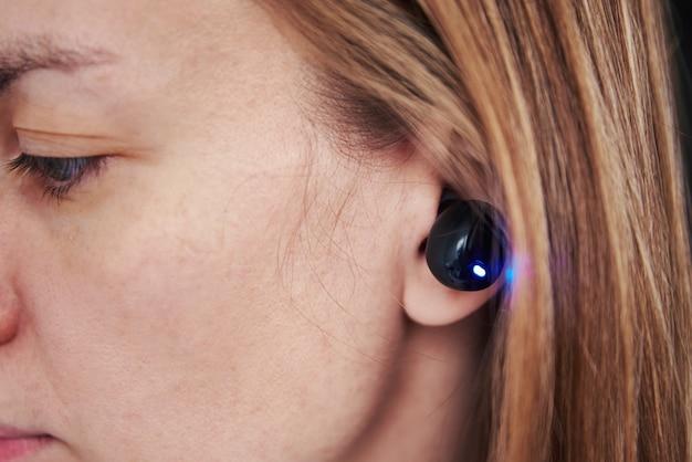 Femme écoutant de la musique grâce à des écouteurs sans fil. caucasian woman using bluetooth headhones dans l'oreille, gros plan