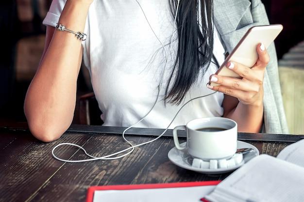 Femme écoutant de la musique par smartphone.