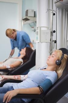 Femme écoutant de la musique pendant sa transfusion