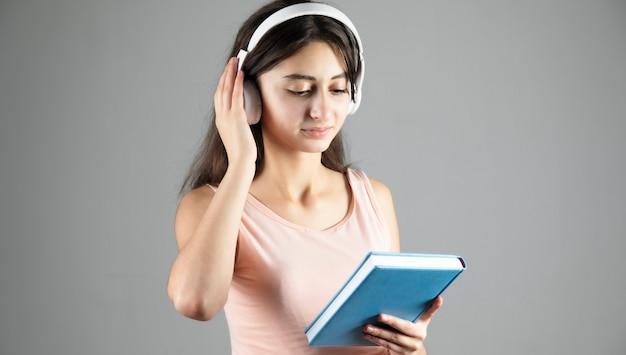 La femme écoute un livre avec des écouteurs