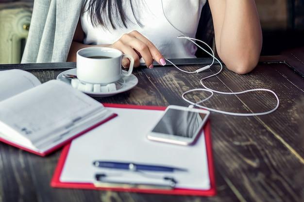 La femme écoute de la musique avec des écouteurs avec une tasse de café dans le café.