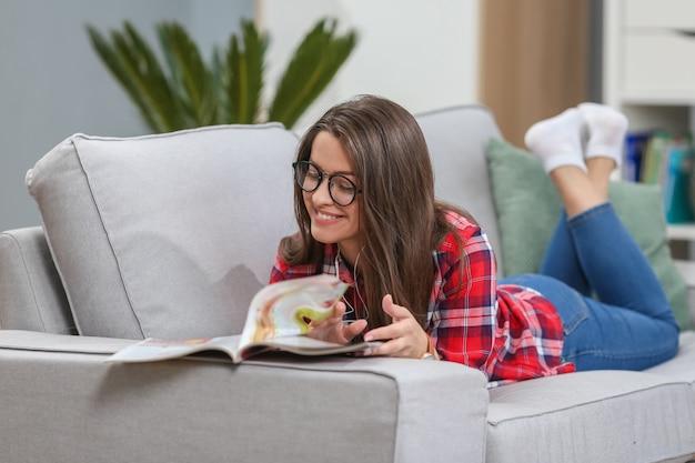 Femme écoute de la musique et lit un magazine