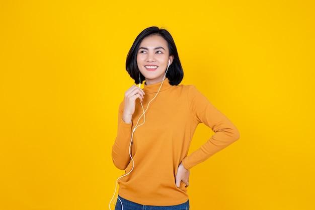Femme avec écouteur pour écouter des musiques sur fond jaune