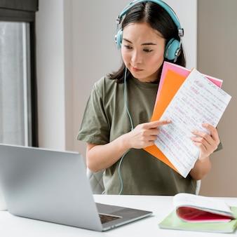 Femme avec des écouteurs ayant un appel vidéo sur ordinateur portable