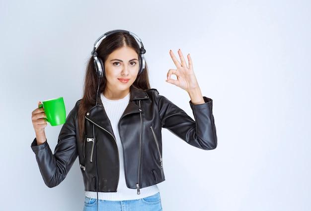 Femme avec des écouteurs ayant une tasse de thé vert.