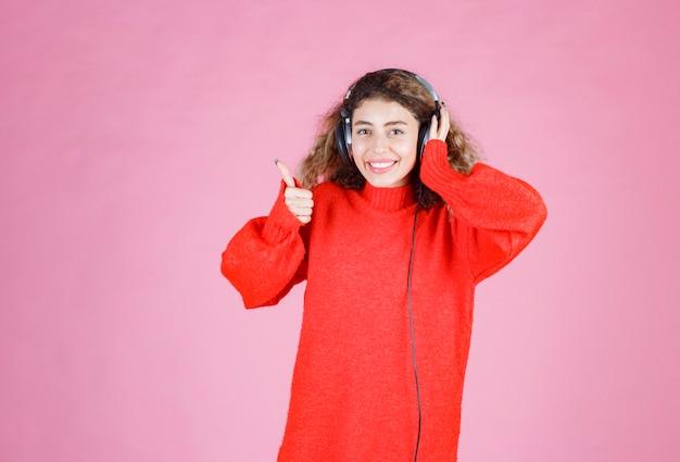 Femme avec des écouteurs écoutant et appréciant la musique.