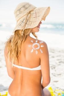 Femme avec un écran solaire sur sa peau