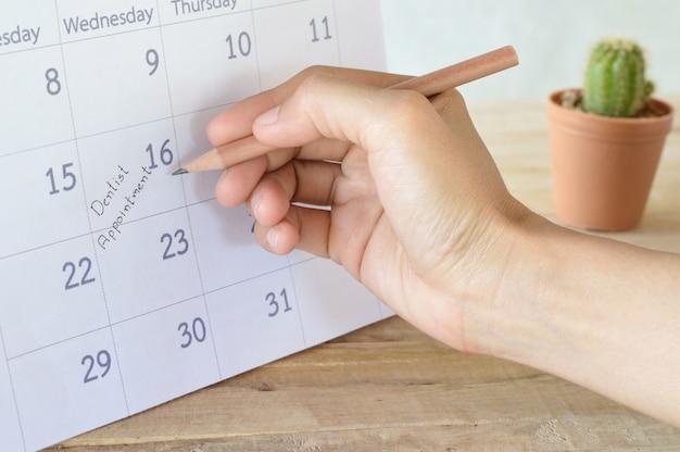 Femme écrire dentiste rendez-vous dans le calendrier calendrier
