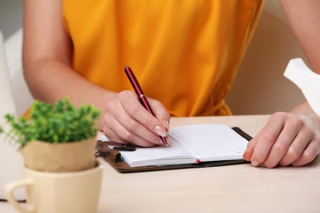 Femme écrire sur ordinateur portable sur le lieu de travail se bouchent